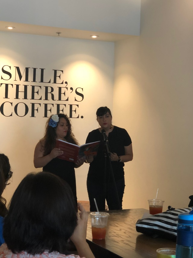 Photo of Aideed Medina and Marisol Baca sharing a bilingual poem at Readers for RAICES