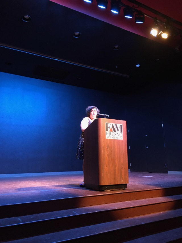 Photo of writer Randa Jarrar reading her work on the Fresno Art Museum stage