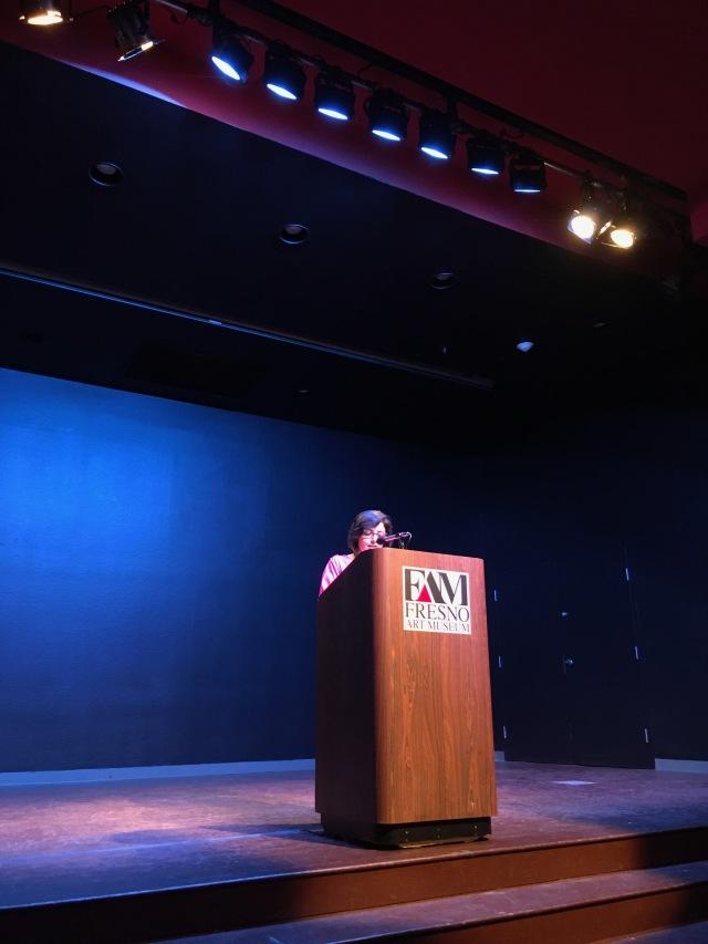 Photo of writer Samina Najmi reading her work on the Fresno Art Museum stage