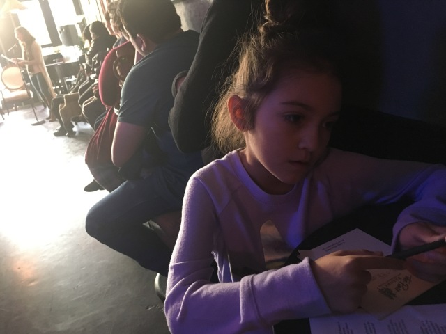 Photo of child writing poetry at a literary reading