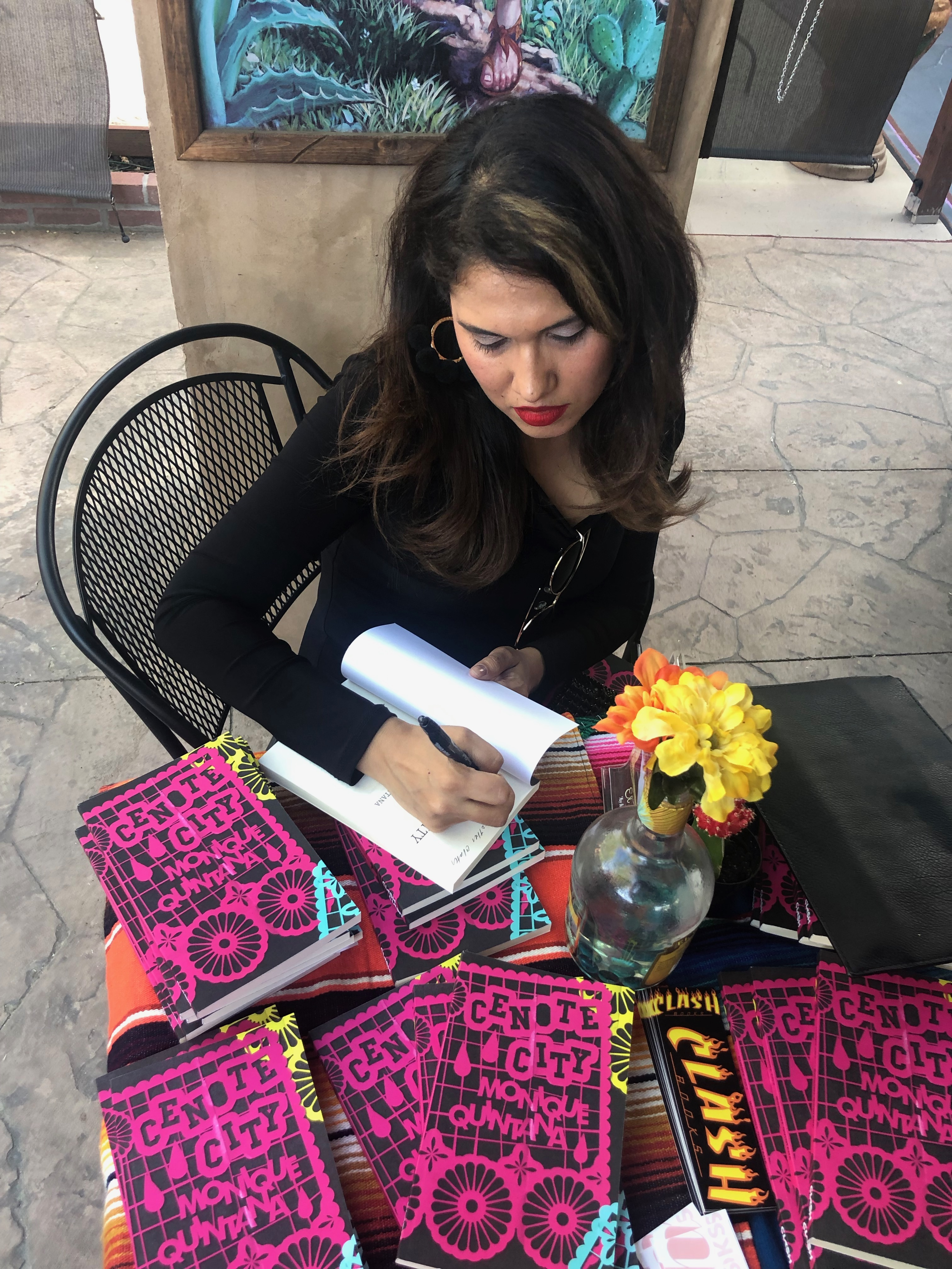 Photo of Monique Quintana signing books at the Cenote City book launch