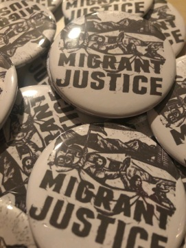 Close-up photo of buttons created by BakaGirlJewelry for the event. Buttons say Migrant Justice in all-caps, with drawing of people with arms raised and mouths open.